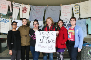 "Clothesline Project participants hold up message: ""Break the Silence"""